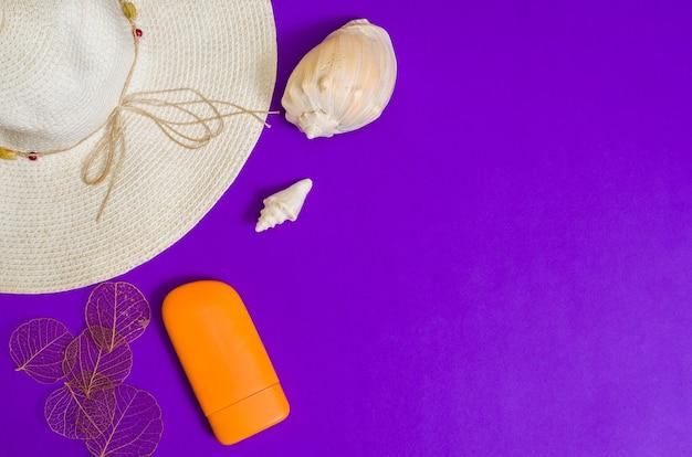 紫色の表面のビーチアクセサリー、コピースペース。休暇、上面図、休暇、旅行アイテムの概念