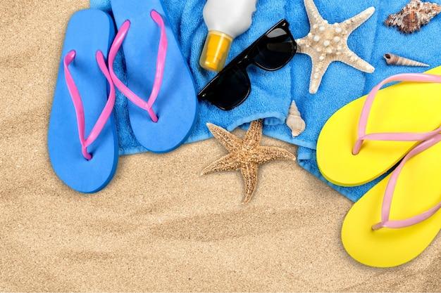 모래에 비치 액세서리입니다. 슬리퍼, 선글라스, 불가사리, 수건