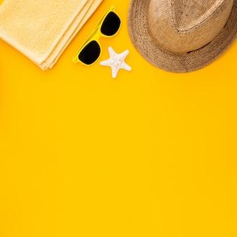 黄色の背景にビーチアクセサリー。ヒトデ、サングラス、タオル、縞模様の帽子。