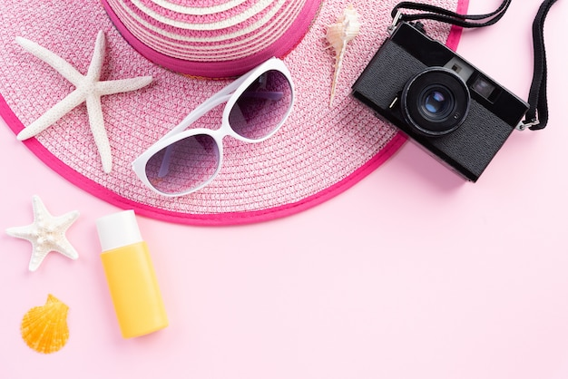 Beach accessories on pink background for summer concept