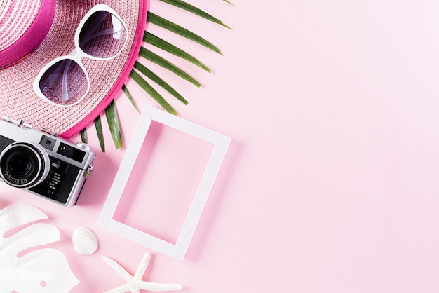 Beach accessories on pink pastel background for summer holiday concept.