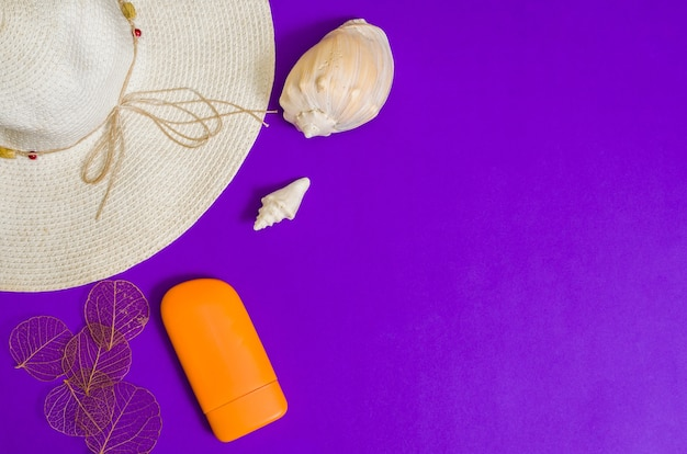 Beach accessories on purple surface, copy space. concept of vacations, top view, vacation and travel items