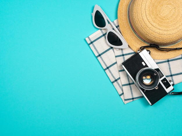 Beach accessories retro film camera, sunglasses, starfish beach hat and sea shell on blue background for summer holiday and vacation