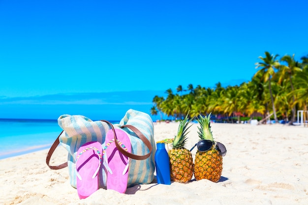 Beach accessories on sand for summer vacation concept. bag, flip flops, tropical pineapples cocktails pina colada and sunscreen lotion bottle on caribbean beach. saona island, dominican republic.