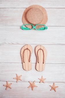 ビーチアクセサリー。夏の靴-ビーチサンダル、太陽の帽子、ヒトデ、サングラス