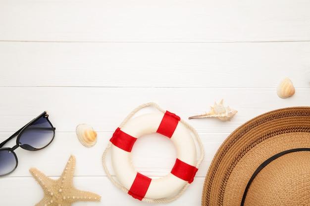Beach accessories on white wooden background.