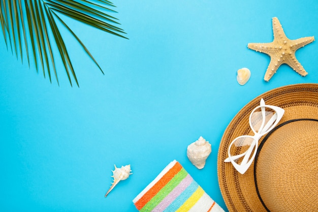Beach accessories with palm leaves on blue background