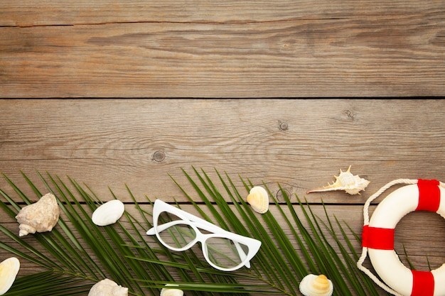 Beach accessories with palm leaves on grey wooden background