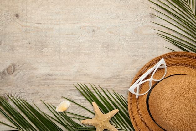 Beach accessories with palm leaves on light background