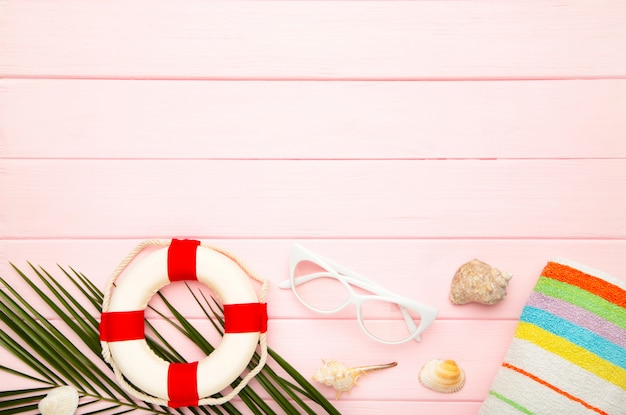 Beach accessories with palm leaves on pink background