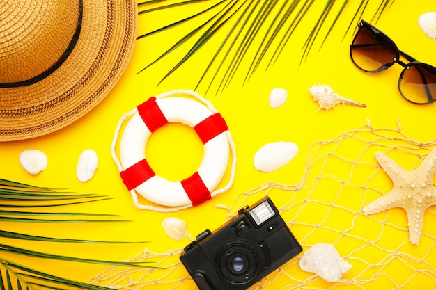 Beach accessories with palm leaves on yellow background