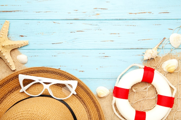 Beach accessories with sand on blue background