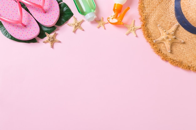 Beach accessories with straw hat, sunscreen bottle and seastar on pink background top view with copy space.