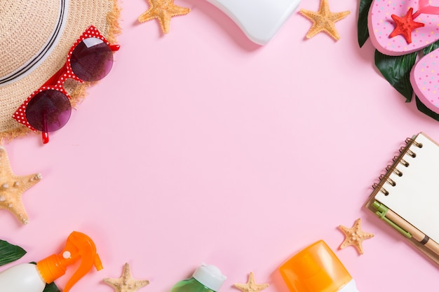 Beach accessories with straw hat, sunscreen bottle and seastar on pink wall top view with copy space