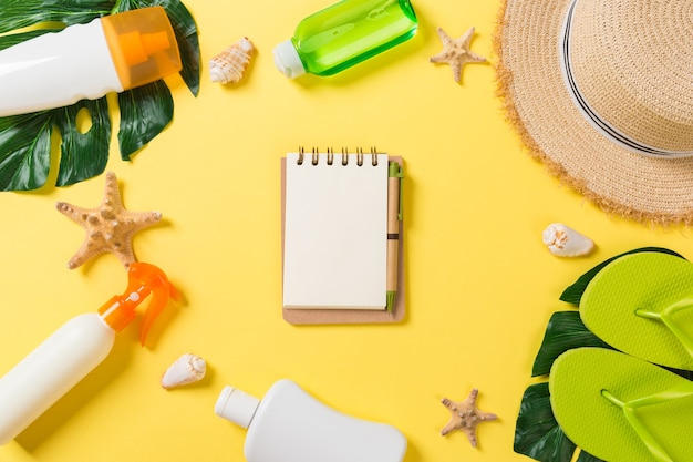 Beach accessories with straw hat, sunscreen bottle and seastar on yellow background top view with copy space.