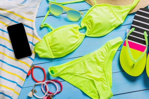 黄色の水着、サングラス、ビーチサンダルを備えたビーチアクセサリー