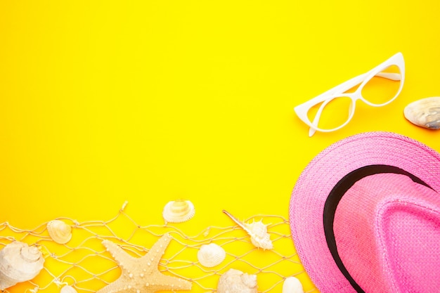 Beach accessories on yellow background with copy space