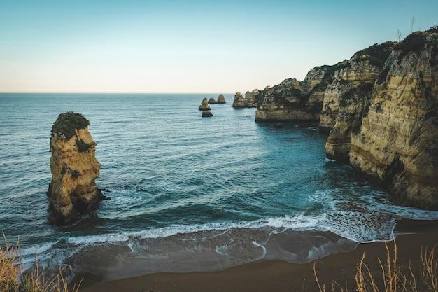 Пляж среди каменных утесов на берегу атлантического океана
