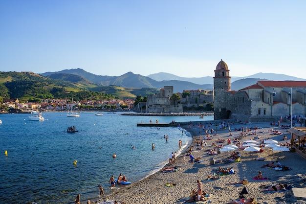 Пляж и замок в средневековом порту с лодками и людьми. концепция путешествия