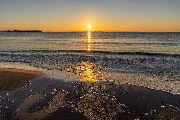 日の出のビリャホヨサの町のビーチと港