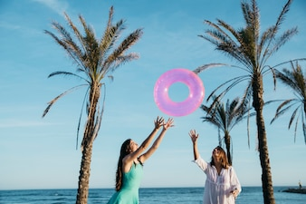 Beach and summer concept with joyful women and palm trees