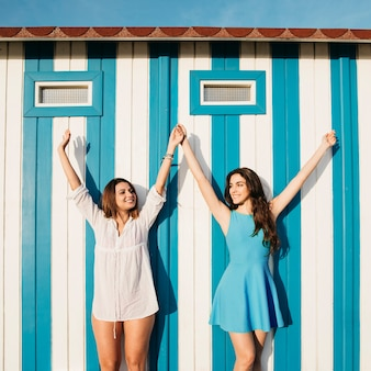 Beach and summer concept with women raising arms