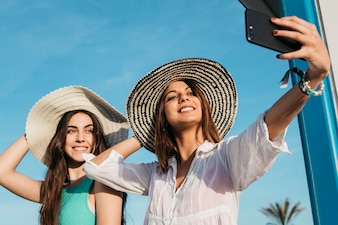 Beach and summer concept with women taking selfie with smartphone
