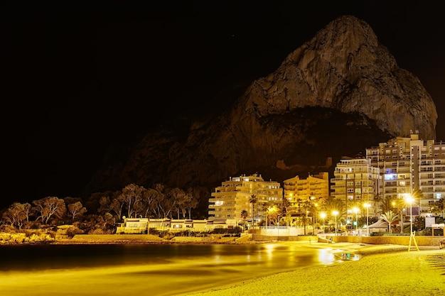 照らされた建物と海の隣の背景に大きな山がある夜のビーチ。カルペアリカンテ。