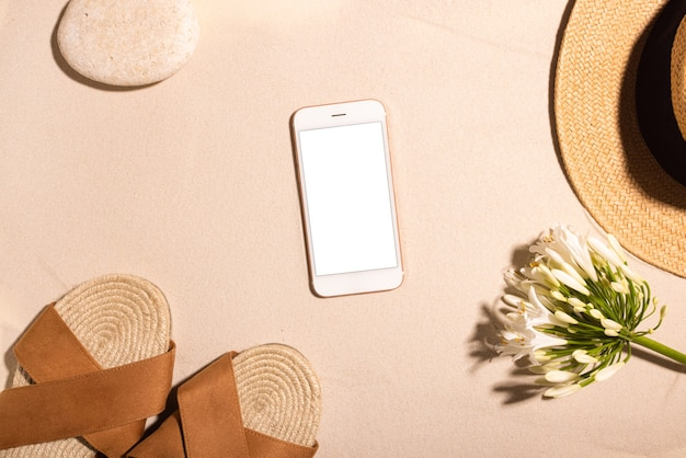 携帯電話の茶色のサンダルと太陽の概念の合計の砂浜の石とビーチの背景...