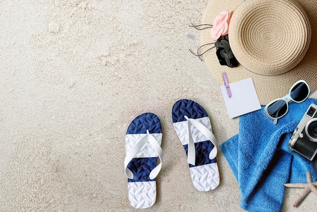 Beach background with sandals, straw hat, towel and camera, top view