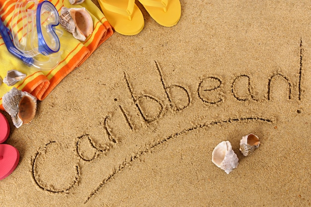 Beach background with towel and flip flops and the word caribbean written in sand