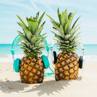 Tiri il fondo in secco con due ananas che indossano le cuffie