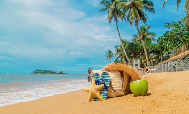 Beach bag and coconut at sea.