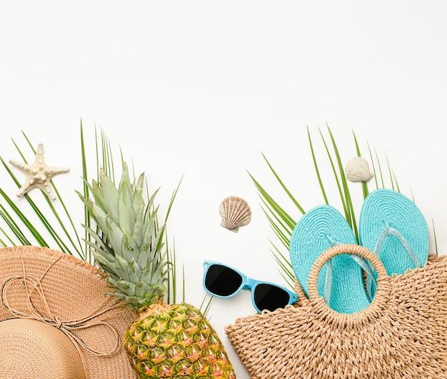 복사 공간이 있는 밝은 배경에 비치백, 태양 모자, 파인애플, 플립플롭, 야자수 잎, 선글라스, 조개, 불가사리