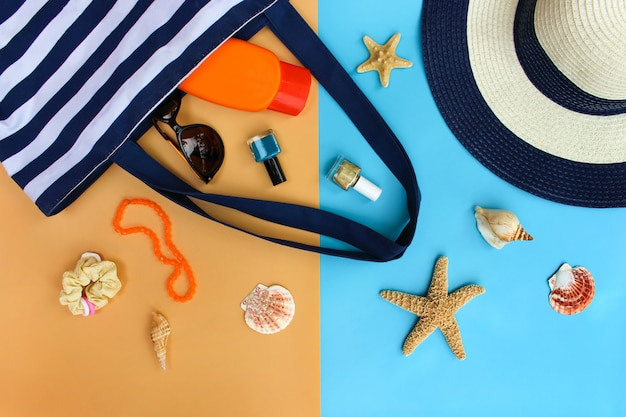 Beach bag, sun hat, sunblock, beads, shells, sunglasses, hair scrunchies, nail polish. top view.