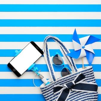 白と青の背景にビーチバッグ、サングラス、スマートフォン。上面図、フラットレイ。