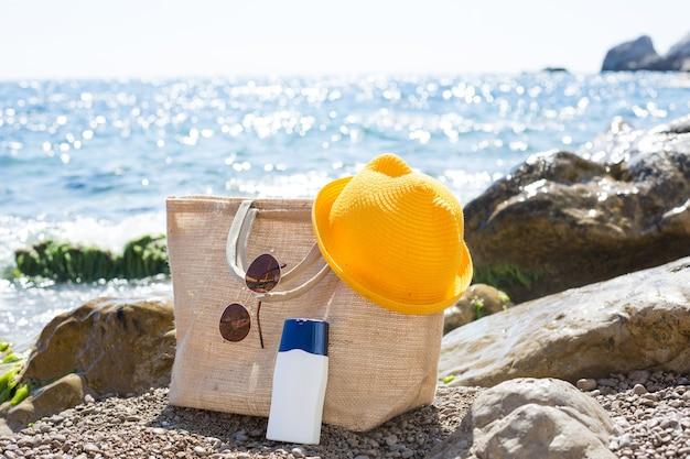 海の近くの小石のビーチに日焼け止めの白いチューブが付いているビーチバッグ。モックアップ。