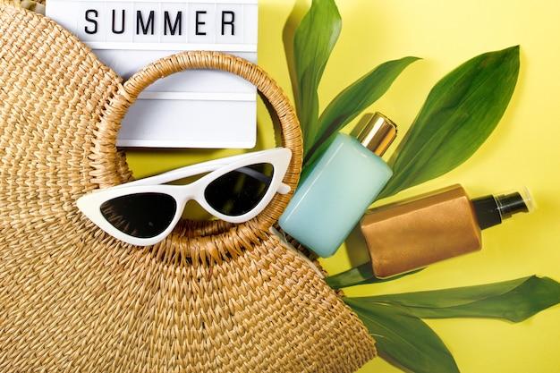 色付きの背景の上面図にビーチアクセサリーが付いたビーチバッグ。日焼け止め、メガネ。