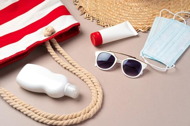 Пляжная сумка с пляжными принадлежностями и медицинской защитной маской на бежевом цвете