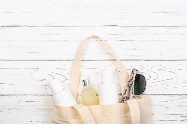 化粧品、日焼け止め、白い木の板にサングラスが付いているビーチバッグ