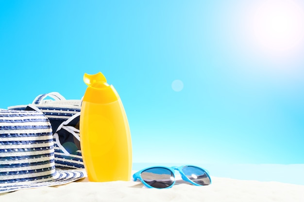 Beach bag with leisure accessories and hat on the sandy beach. blue sky with copy space