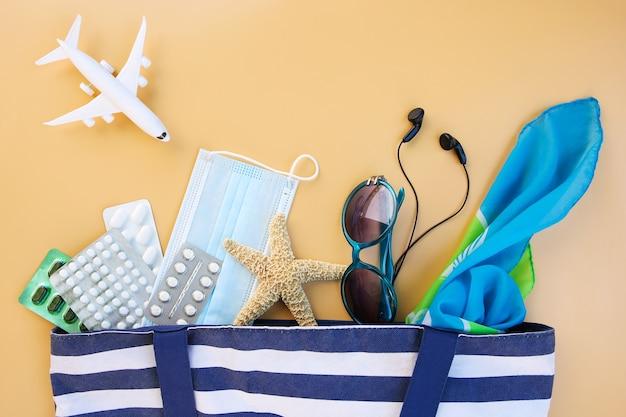 Пляжная сумка, женские аксессуары, таблетки и защитная медицинская маска на бежевом фоне. вид сверху.