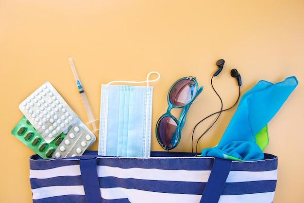 Пляжная сумка, женские аксессуары, таблетки, шприц и защитная медицинская маска на бежевом фоне. вид сверху.