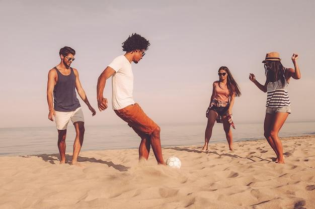 ビーチボール。海を背景にビーチでサッカーボールで遊ぶ陽気な若者のグループ
