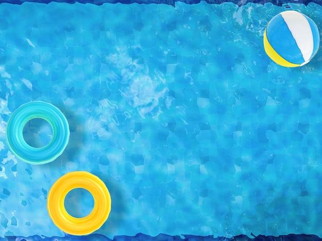Пляжные мячи и плавательные кольца, плавающие на вид сверху на бассейн с пустым пространством