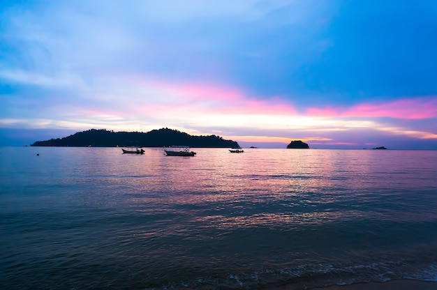 Пляж, красивый фиолетовый закат на море с холмами