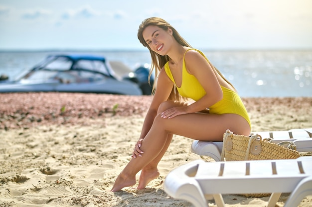On a beach. a beautiful young woman in a yellow swimming suit sunbathing