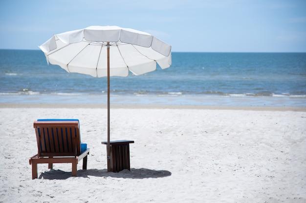 Пляжная кровать с зонтиком на фоне океана в хуахине, таиланд