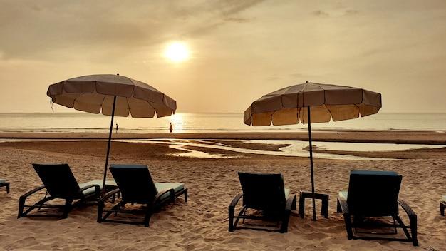 美しい海の日の出の時間とビーチの傘の下のビーチベッド