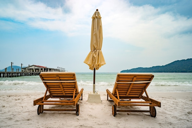 Beach calm scene with sunbeds and straw umbrellas under coconut palms close to sea. tropical paradise with chaise lounges on white sand, beautiful travel card background